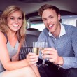 Happy couple drinking champagne in limousine — Stock Photo #65277479