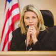 Portrait of a serious judge with american flag behind her — Stock Photo #65279209