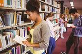 Students reading book against bookshelves — Stock Photo
