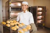 Baker smiling at camera holding rack of rolls — Stock Photo