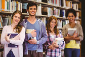Happy students holding books in row — Stock Photo