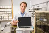Happy pharmacist showing laptop screen — Stock Photo
