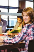 Smiling student sitting at desk looking — Stock Photo