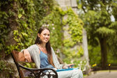 Smiling student sitting on bench holding her mobile phone — Stock Photo