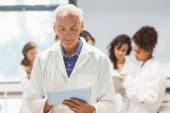 Science lecturer holding tablet pc in lab  — Stock Photo