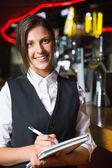 Happy barmaid smiling at camera taking notes — Stock Photo