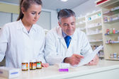 Pharmacist showing a prescription to his trainee — Stock Photo