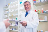 Pharmacist handing a prescription to somebody — Stock Photo