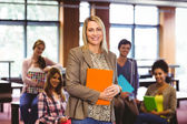 Portrait of the professor with students behind her — Stock Photo