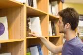 University student choosing books on bookshelves — Stock Photo