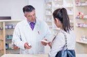 Customer handing a prescription to a pharmacist — Stock Photo