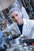 Smiling scientist using brewer in the container — Stock Photo