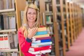 Mature student in library holding books — Stock Photo