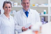 Pharmacist and his trainee looking at the camera — Stock Photo