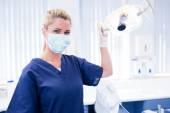Dentist in mask holding light — Stock Photo