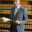 Lawyer holding book in the law library — Stock Photo #65281445