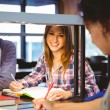 Happy student sitting at desk writing smiling — Stock Photo #65282375