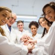 Science students and lecturer putting hands together — Stock Photo #65283311