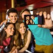 Portrait of happy friends taking a photo with a phone — Stock Photo #65284447