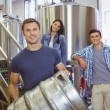 Young man holding keg with these colleagues behind him — Stock Photo #65284573