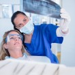 Dentist in mask explaining x-ray to patient — Stock Photo #65285365