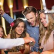 Drunk friends watching barman pouring cocktail — Stock Photo #65285511