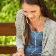 Smiling student sitting on bench listening music and using lapto — Stock Photo #65286663