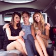 Pretty girls with ladies man in the limousine — Stock Photo #65288013