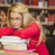 Thoughtful mature student leaning on a stack of books — Stock Photo #65289749