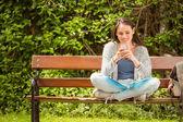Allievo sorridente che si siede sulla panchina testo messaggio sul suo fon mobile — Foto Stock