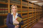 Female librarian posing and holding a book — Stock Photo