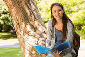 Smiling student sitting on trunk and holding book — Stock Photo