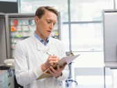 Handsome pharmacist writing on clipboard — Stockfoto