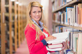 Mature student picking out book in library — Stock Photo