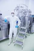 Scientist in protective suit leaning against machine — Stock Photo