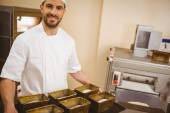 Happy baker holding tray of loaf tins — Stock Photo