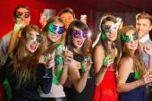 Friends in masquerade masks drinking champagne — Stock Photo