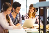 Student looking at camera while studying with classmates — ストック写真