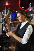 Happy barmaid pulling a pint of beer — Stock Photo