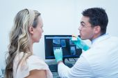 Dentist showing woman prosthesis teeth — Stock Photo