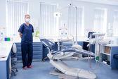 Dentist in blue scrubs standing beside chair — Stock Photo