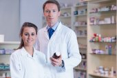Pharmacist showing medication to his trainee — Stock Photo