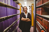 Unsmiling lawyer standing between shelfs with arms crossed — Fotografia Stock