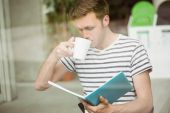 Student drinking a hot drink and holding book — Stock Photo