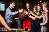 Happy friends drinking shots by the dj booth — Stock Photo