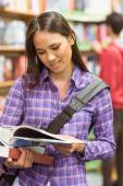 Smiling university student reading textbook — Stock Photo