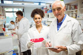 Lecturer and student smiling at camera in the lab — Stock Photo