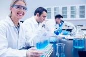 Science student using pipette in the lab to fill test tubes — Stock Photo