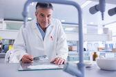 Smiling biochemist preparing some medicine — Stock Photo