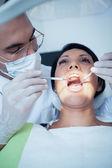 Male dentist examining womans teeth — Stock Photo